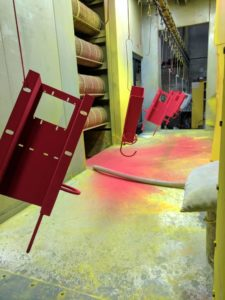 Conveyor parts in powder coating booth going red.